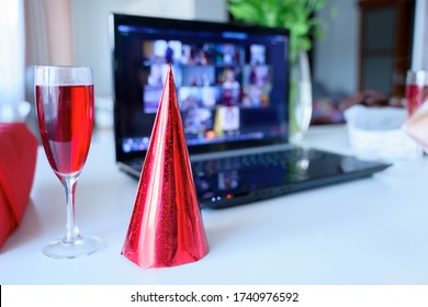 Red holiday hat,glass of juice.Kids virtual birthday party.Celebration of holiday at home on isolation.Online conference,video call in laptop,computer.Animator,cookies.Quarantine,coronavirus covid-19. - Shutterstock ID 1740976592