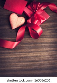 REd Holidays gift and heart on wooden background/ Valentines day background