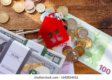 Red home house keys on the banknotes and coins background euro pile pack real estate concept expenses property buying mockup copy space close up background selective focus