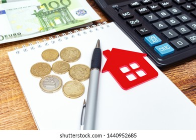 Red home house notepad pen on the banknotes and coins background euro pile pack real estate concept expenses property buying mockup copy space close up background selective focus