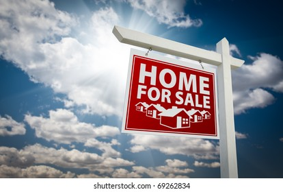 Red Home for Sale Real Estate Sign Over Beautiful Clouds and Blue Sky.