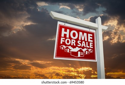 Red Home For Sale Real Estate Sign Over Beautiful Clouds and Sunset Sky.