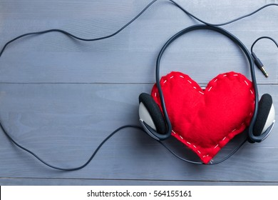 Red homemade heart with headphones on Valentine's Day. Love for music abstract concept. Copy space on the left.