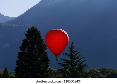 Red hot air balloom flying low over Lake Annecy France
