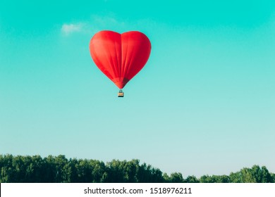 Red hot air balloon in the shape of a heart against the blue sky and some light clouds. Concept of love and peace.