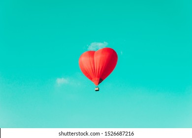 Red hot air balloon in the shape of a heart against the blue sky and some light clouds. Concept of love, romantic and travel. Happy Valentine's Day.