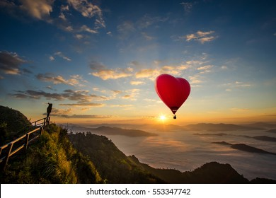 Red hot air balloon in the shape of a heart, Colorful hot-air balloon flying over the mountain