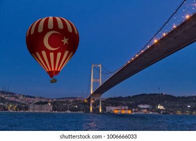 Red Hot Air balloons flying over Bosphorus Bridge at night. Istanbul, Turkey