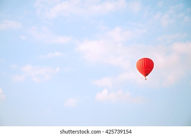 Red hot air bal?oon flying in blue sky with white clouds