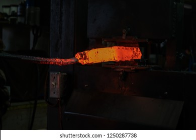 A red hot billet of metal is being worked in the blacksmith shop.