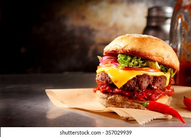Red hot chili cheeseburger with a spicy chilli pepper sauce and melting cheese over a juicy beef patty on a crusty bun served on brown paper, with copyspace