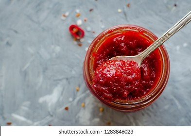 Red hot chili jam in glass jar with fresh ingredients on grey concrete background. Natural homemade peppers sauce with spoon. Fresh Homemade salsa dip. Top view. Copy space.