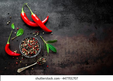 red hot chili pepper corns and pods on dark vintage metal culinary background, top view
