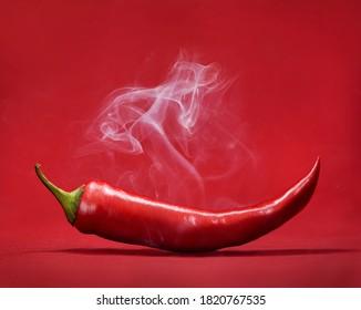 Rote scharfe Chilischoten auf rotem Hintergrund mit Rauch. Stillleben mit mexikanischem Paprika-Gewürz.