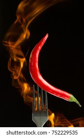 Red hot chili pepper on the folk with fire, black background
