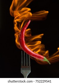 Red hot chili pepper on the folk with body of flame, black background