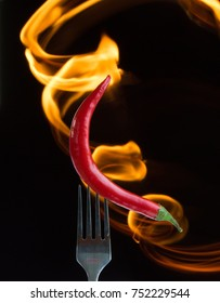 Red hot chili pepper on the folk with tonge of flame, black background