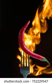 Red hot chili pepper on the folk with flame, black background
