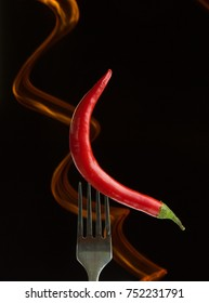 Red hot chili pepper on the metal folk and body of flame on black background