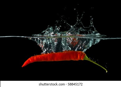 Red hot chili pepper splashing into water.