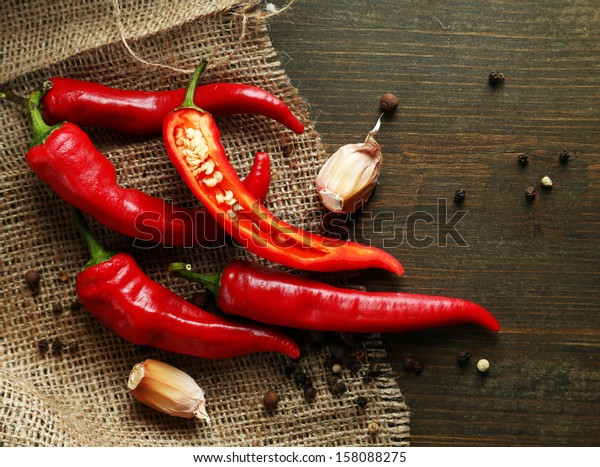 Red hot chili peppers  and garlic, on sackcloth,  on wooden background
