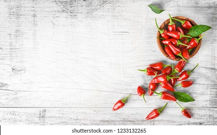 Red hot chili peppers on white table copy space. Spicy pepper in bowl top view, banner or panorama concept.