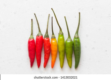 Red Hot Chili Peppers On Background or White Table. A Lot of Red Chilli Peppers. Green, Yellow Hot Chili Peppers. Copy space for your text. Flat lay, top view. Colorful chili pepper rainbow. Gradient.