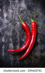 Red hot chili peppers over black metal background. Top view.