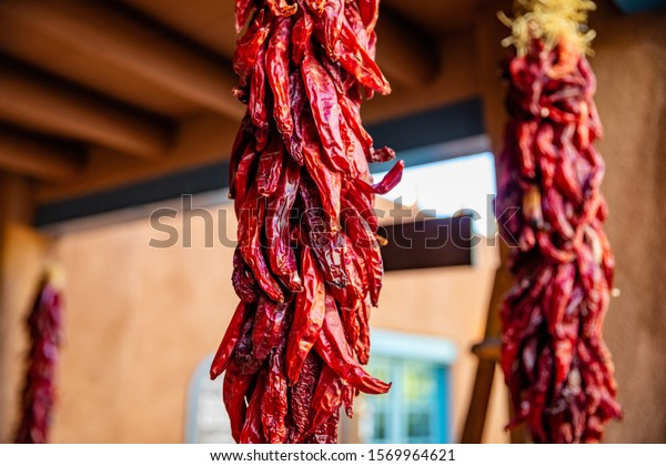 Red hot chili peppers ristras dried bunch hanging on a traditional building entrance, Santa Fe New Mexico