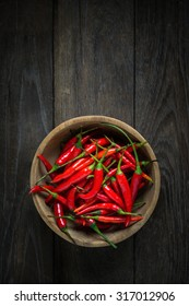 Red Hot Chili Peppers in wooden bowl on old wooden background, Overhead view of chili pepper on wood background