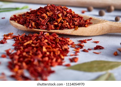 Red hot chillies pepper flakes in wooden spoon on white textured background, top view, close-up, selective focus.