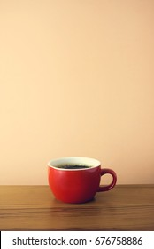 red hot coffee cup with wood background table