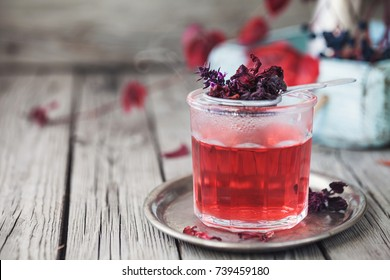 Red Hot Hibiscus tea in a glass cup on wooden table