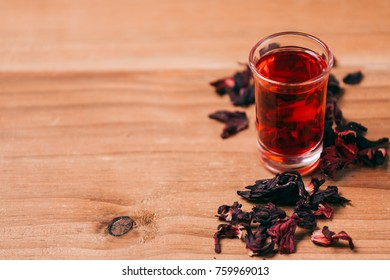 Red hot hibiscus tea in a glass mug on a wooden table