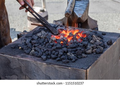 Red hot metal being forged in a blacksmiths fire in a smithy next to an anvil.