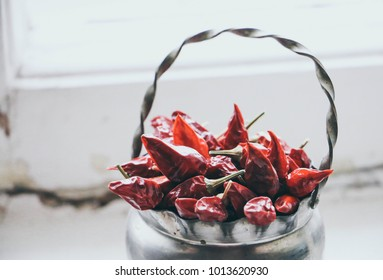 red hot pepper in a metal vase at an old window, shabby chic, copy space.