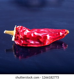 Red hot pepper over black reflecting background, square image