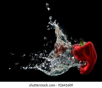 A red hot pepper splashing into water isolated on black background