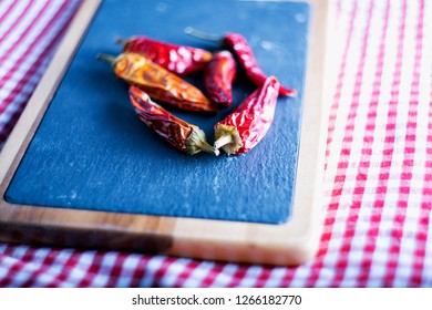 Red hot peppers over cutboard, shallow depth of field, horizontal image