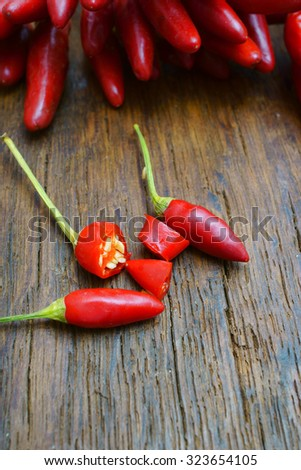 Red hot sliced chili pepper pods on old rustic wooden table