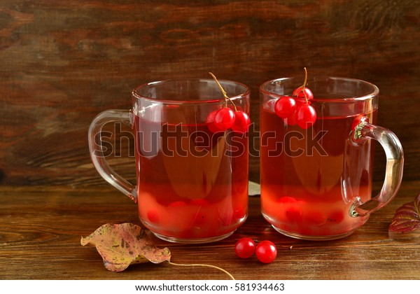 Red hot tea with viburnum berries in a glass cup