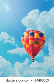 Red hot-air balloon on background of blue sky and clouds