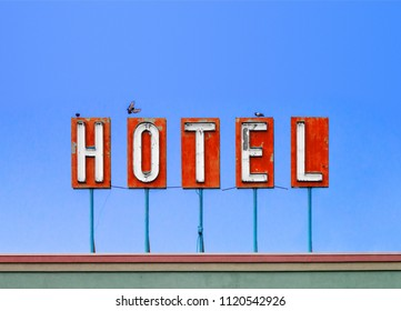 Red hotel sign on top of a dirty old motel isolated on blue sky background with birds