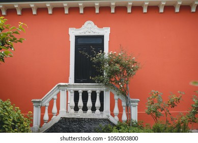 red house with black door and stairs with fence