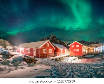 Red house in fishing village with aurora borealis over arctic ocean in winter at night. Reine, Lofoten islands, Norway