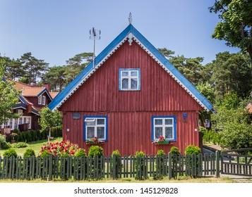 Red house with green fence on Curonian Spit, Lithuania
