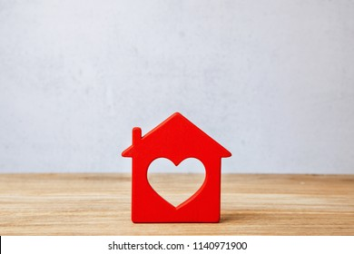 Red House with heart, sweet home. Symbol of house on wooden wall on gray wall background. Copy space for text