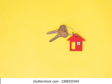 Red house key on yellow background. Minimal creative style.