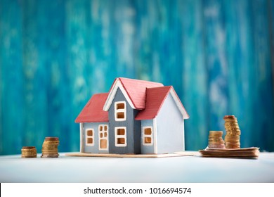 Red house model on wooden background with banknotes and coins.