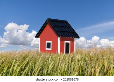 A red house on the field with a blue sky in the background. Good for concepts as for new house